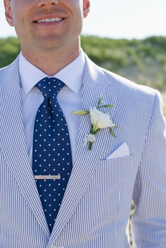Groom wearing white and blue polkadot neck tie with white and blue pin stripped stuit