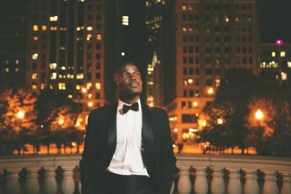 Man wearing a tux standing on a bridge looking up into the night sky with Chicago city building in the back ground.