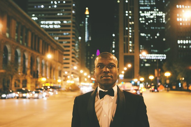 Man standing outside on a Chicago street wearing a tux looking off into the distance