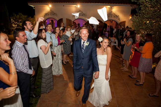 Bride and groom grand exit while guests throw paper airplanes overhead