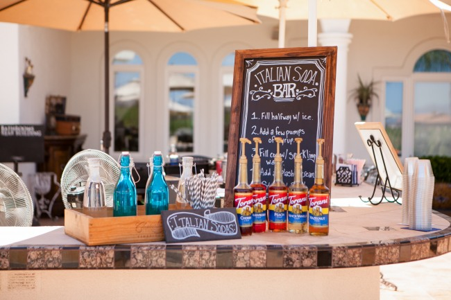 "Wedding cocktail bar with gray paper straws, blue bottles, and a sign with ""Italian Sodas"""
