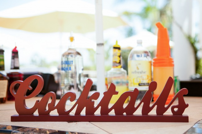 "Red wooden sign spelling ""cocktails"" for wedding cocktail hour decor"