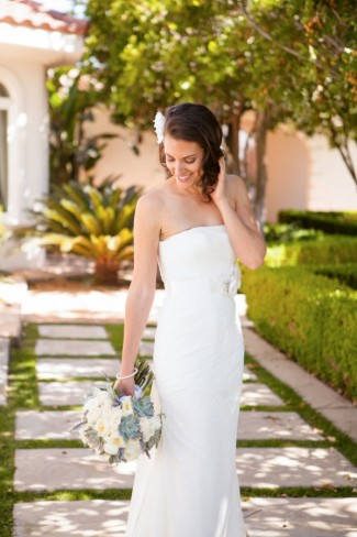 Bride wearing strapless sheath with white flower in hair and holding bridal bouquet.
