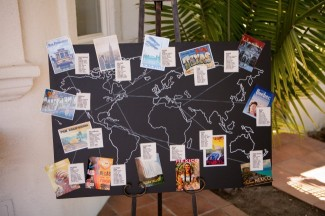 A black world map with postcards from all over the world taped on