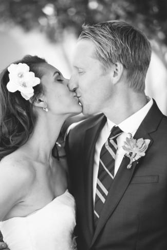black and white photo of bride kissing groom with his succulent boutonniere