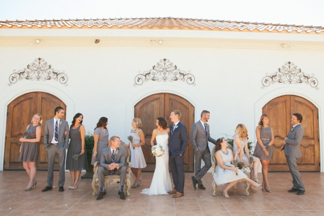 bridal party dressed in gray at wood doors of Villa de Amore Vineyard