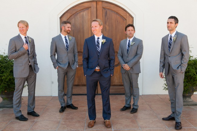 groom in blue suit standing with groomsmen wearing gray suits