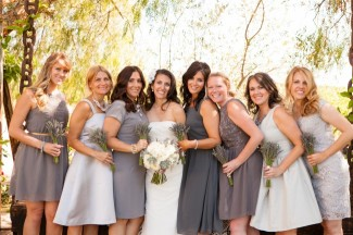 bride in strapless sheath standing with 7 bridesmaids all wearing gray mismatched gowns
