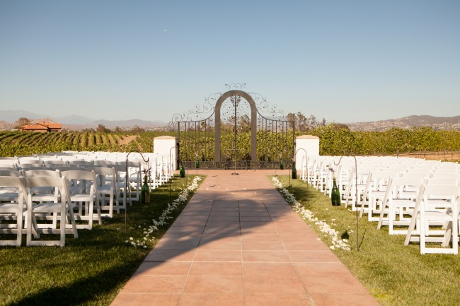 Ceremony aisle for vineyard wedding at Villa de Amore lined with shepherd hooks with hanging green bottles