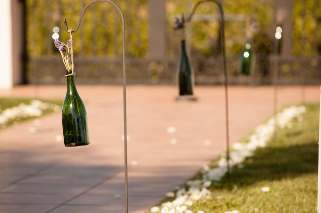 Villa de Amore ceremony aisle with white rose petals and wine bottles hanging from shepherd hooks