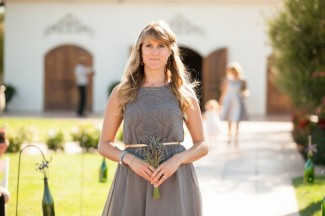bridesmaid walking down aisle for vineyard wedding at Villa de Amore holding lavender bouquet