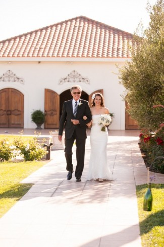 Bride in strapless sheath gown walking down aisle with her father for wedding at Villa de Amore