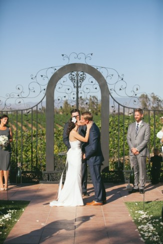 bride and groom kissing during wedding ceremony in front of vineyard at Villa de Amore
