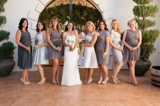 bride standing with bridesmaids all wearing mismatched gray dresses