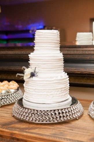 3 tier white layer cake on a round silver crystal pave cake stand