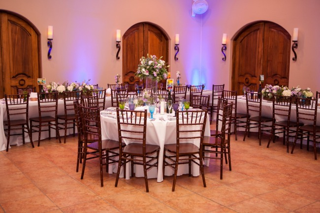 Indoor wedding reception with round table with multi color wine glasses, white table cloth and brown chairs