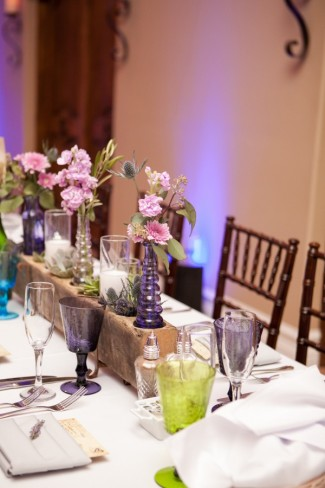 Wedding reception table with multi color wine glasses, purple vases with pink flowers and white candles