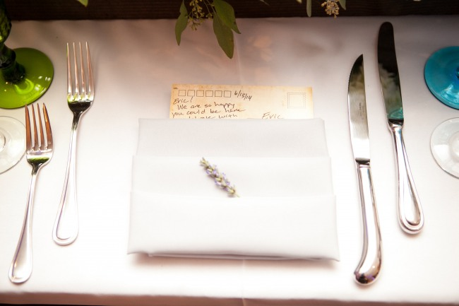 Wedding reception place setting with white folded napkin, a piece of lavender, and a postcard