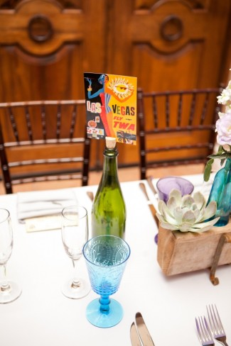 Green wine bottle with a Las Vegas post card stuck in cork as wedding reception decor