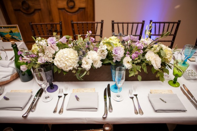 Wedding reception place setting with colorful wine glasses, a white and purple floral centerpiece