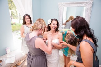 Bride getting ready with bridesmaids wearing mismatched grey dresses