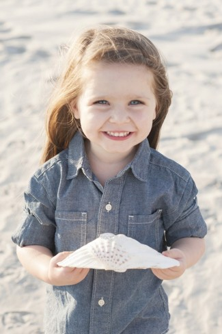 daughter holding seashell on the beach