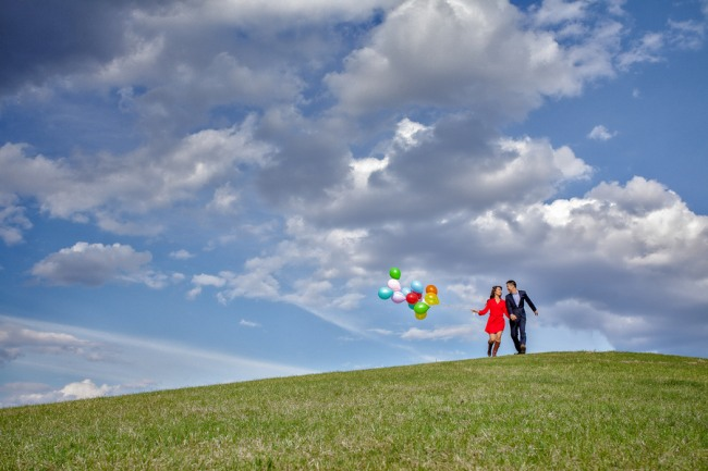 Couple holding hands walking down grassy knoll holding a bunch of colorful balloons