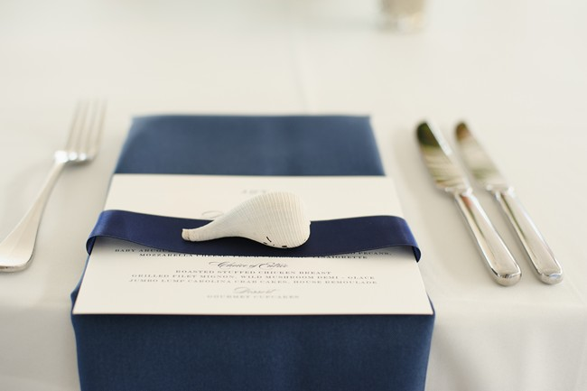 Navy blue folded napkin at wedding reception place setting with a shell on top