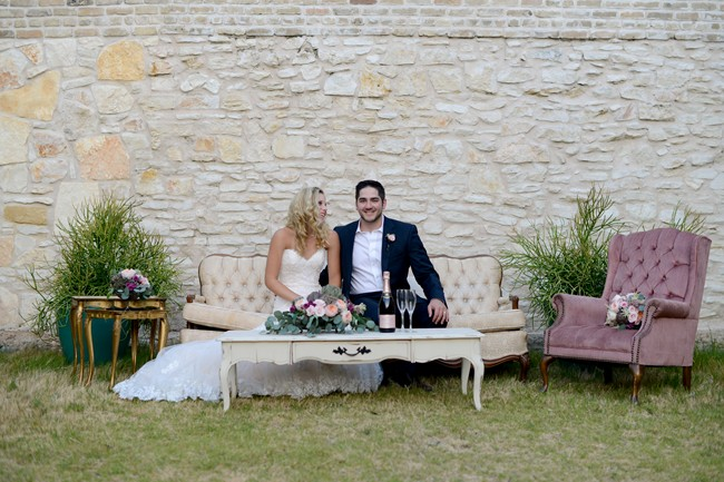 Bride and groom sit on cream colored vintage couch outside Palm Door on Sixth Street & Palm Door on Sixth Street Styled Wedding Shoot pezcame.com