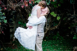 Groom lifting bride off the ground and kissing her