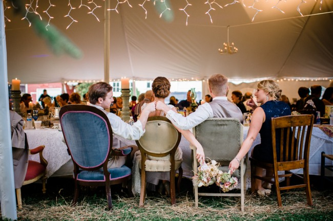 wedding reception under tent with white Christmas lights and mismatched vintage chairs