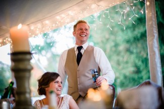 Bride and groom under white tent with hanging Christmas light during wedding reception