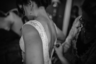 Bridesmaid helping bride put lace bridal gown