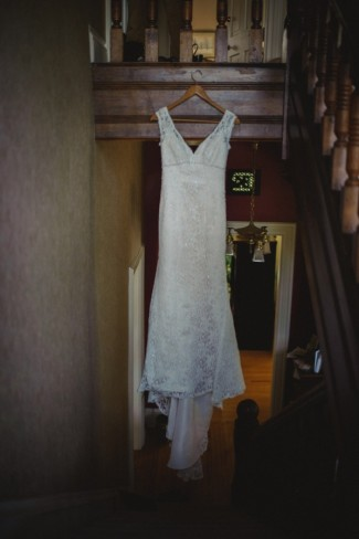 Lace Wedding dress with train hanging from staircase at Apple Tree Lane Bed and Breakfast