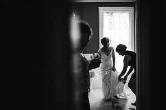 Black and white photo of bridesmaid helping bride put heels