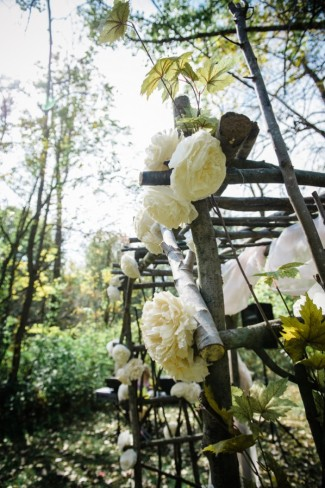 Altar made of branches and large white flowers in woodsy wedding ceremony