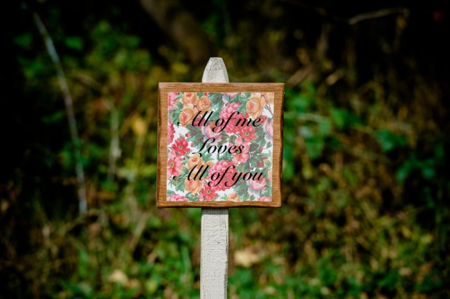 "A sign with floral background saying ""All of me loves all of you"" at Apple Tree Lane B&B wedding"