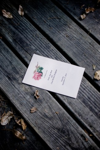 Simple wedding invitation with pink rose laying on wood deck