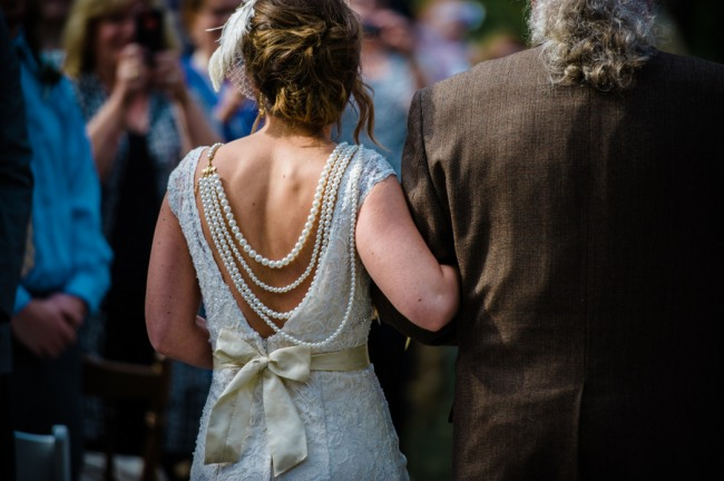 View of brides pearl necklace and sash bow from behind