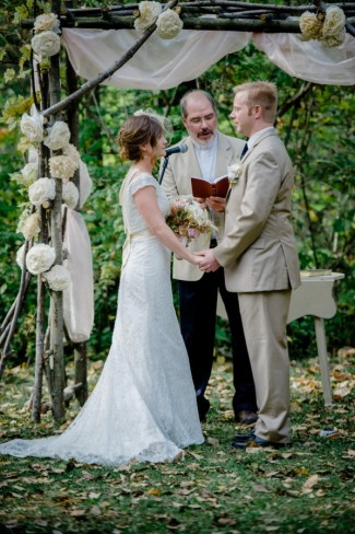 Bride and groom holding hands during ceremony under altar made of branches and white flowers