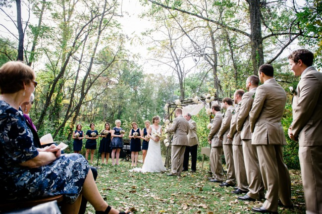 Bride and groom standing at altar made of branches and large white flowers at Apple Tree Lane Bed and Breakfast wedding