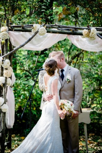 Bride and groom holding hands during ceremony under altar made of branches and large white flowers at Apple Tree Lane Bed and Breakfast Wedding