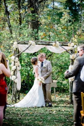 Bride and groom about to kiss during ceremony under altar made of branches and large white flowers at Apple Tree Lane Bed and Breakfast Wedding