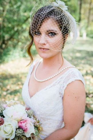 Bride wearing pearl necklace and french netting birdcage veil with feather and flower
