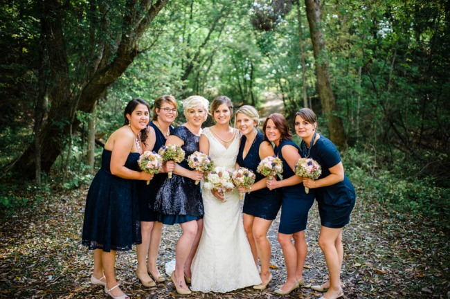 Bride wearing lace gown standing in forest with bridesmaids wearing mismatched navy blue dresses