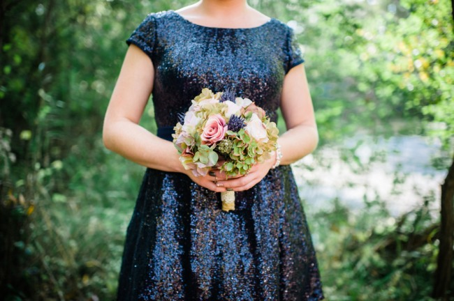 Bridesmaid wearing glittery navy blue dress holding green and pink bouquet