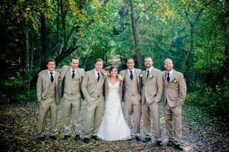 Bride standing with groomsmen wearing tan color suits and black ties in forest