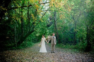 Bride and groom holding hands in forest behind Apple Tree Lane B&B