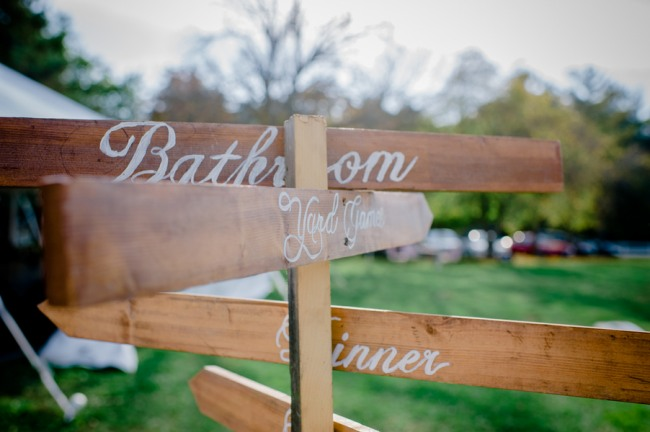A wooden sign with arrows pointing to bathroom, yard games, dinner