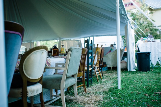 Mismatched wedding reception chairs under white tent